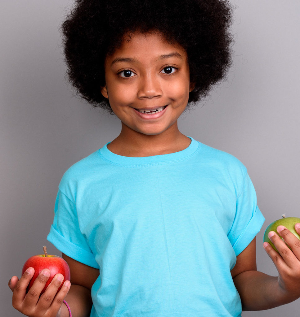 an image of a young african american little girl holding two apples in each hand standing in front of a gray backdrop