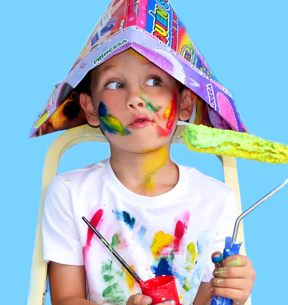 an image of a young boy with paint all over his face, hands, and shirt, sitting in front of a light blue backdrop