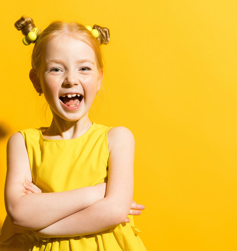 an image of a school aged little girl wearing a bright yellow top with her hair in two bright yellow hair ties standing in front of a yellow backdrop