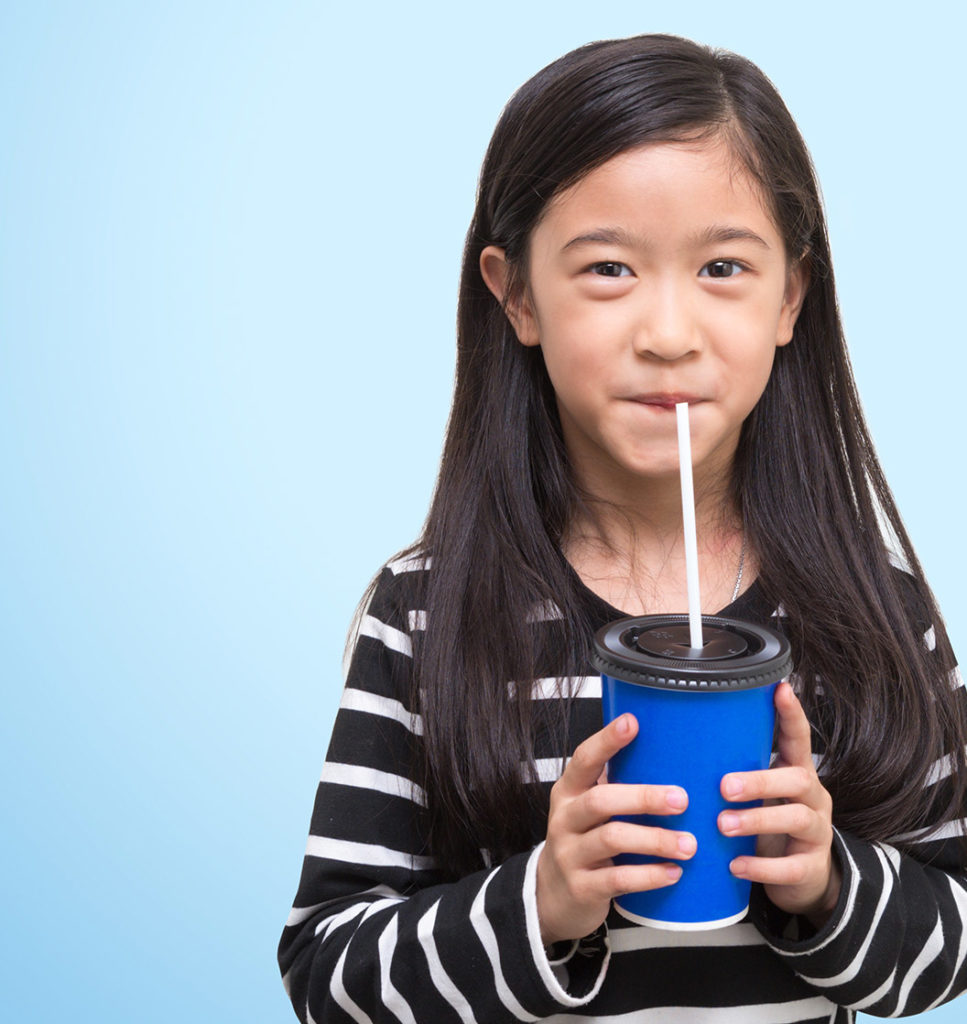 an image of a school aged asian girl drinking something out of a straw standing in front of a light blue backdrop